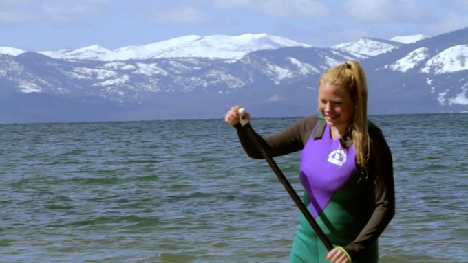 woman wearing wader skins paddling in lake