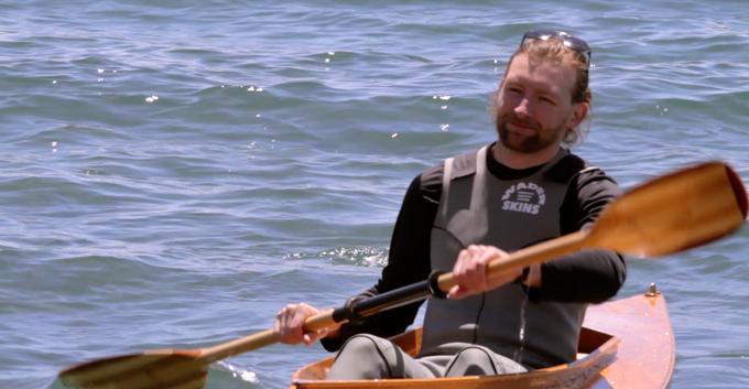 kayaker wearing wader skins paddling in lake