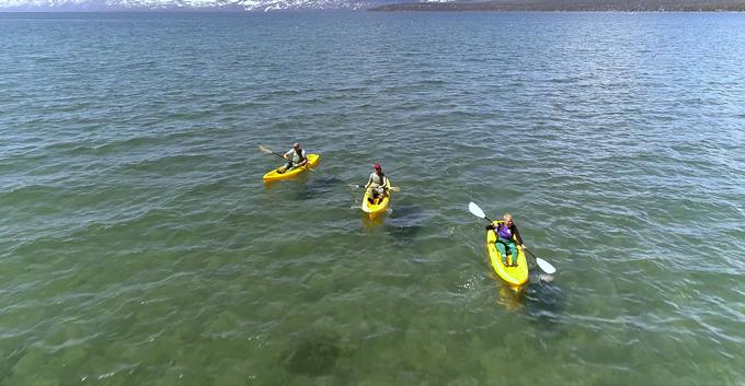 three kayakers in the lake wearing wader skins